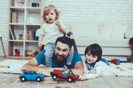 Man Spends Time with His Sons. Father is Engaged in Raising Children. Father and Eldest Sons is Playing with Toy Cars on Carpet. Younger Son is Sitting on Father Back. People is Located in Bedroom. Reklamní fotografie - 127584697