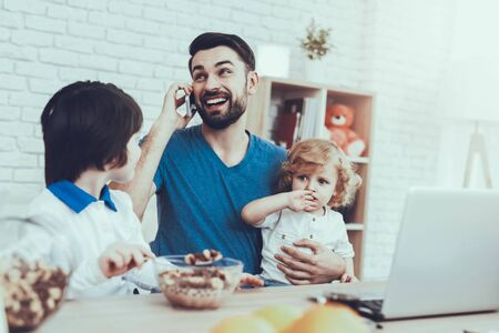 Father is Engaged in Raising Children. Eldest Son is Eating a Breakfast. Father is Working and Talking on Cellphone. Man is Holding a Younger Son. People is Sitting at Table. People Located at Home. Reklamní fotografie - 127781029