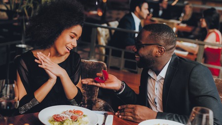 African Handsome Man Proposing to Girlfriend. Romantic Couple in Love Dating. Cutel Man and Girl in a Restaurant. Romantic Concept. Surprised Attractive Woman Getting a Marriage Proposal.