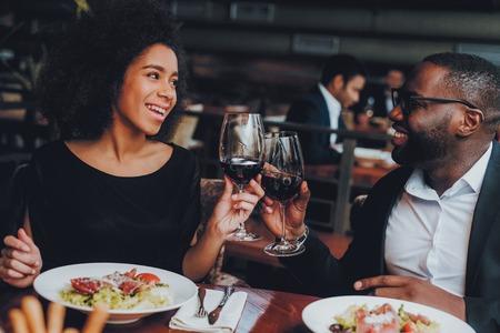 레스토랑에서 데이트 하는 아프리카계 미국인 커플. 사랑 데이트에 로맨틱 커플입니다. 레스토랑에서 메뉴를 주문하는 쾌활한 남자와 여자. 낭만적인 개념입니다. 건배 클래스 레드 와인.