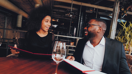 African American Couple Dating in Restaurant. Romantic Couple in Love Dating. Cheerful Man and Woman with Menu in a Restaurant Making Order. Romantic Concept. Anniversary. Date. Love.