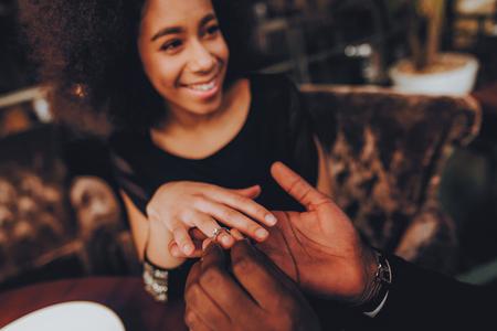 Uomo bello africano che propone alla ragazza. Coppia romantica innamorata Incontri. Cutel uomo e ragazza in un ristorante. Concetto romantico. Donna attraente sorpresa che ottiene una proposta di matrimonio. Squillo.