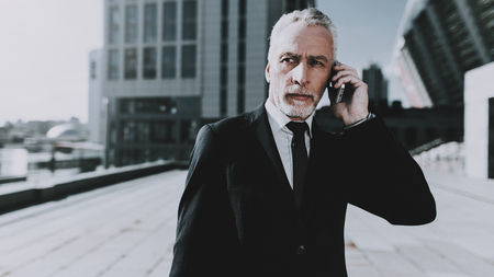 Businessman is Talking on Mobile Phone. Businessman is Old Serious Man. Man Wearing in Black Suit. Man Looking to Distance. Businessman is Standing on Roof of Skyscraper. Sunny Daytime.