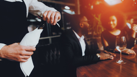 CLose Up Waiters Hand Opening Bottle of Wine. Romantic African American Couple in Love Dating. Cheerful Man and Woman with Menu in a Restaurant Making Order. Romantic Concept. Anniversary.