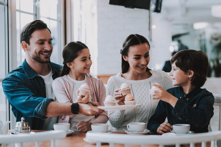 Family Resting in Cafe. Family is a Mother, Father, Daughter and Son. People is Eating Cakes and Drinking a Tea. Persons is Sitting at Table. People is Happy and Smiling. Sunny Daytime.