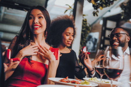 Friends Proposing Marriage to Girls in Restaurant. Group Happy Friends Enjoying Dating in Restaurant. Double Couple Dating in Restaurant. Romantic Couple in Love Dating. Marriage Concept.