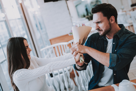 Couple in Cafe. Couple is Beautiful Young Man and Woman. Man is Giving a Bouquet of Flowers to Woman. Woman Dont Want Take a Flowers. Persons is Sitting at Table. Woman is Angry. Man is Upset. Stock Photo