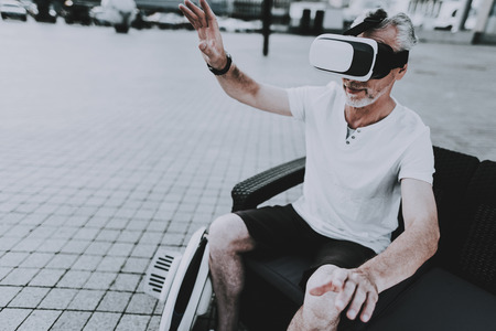 Man is Using a Virtual Reality Glasses. Man is Gesticulating with Hands. Old Smiling Man. Person is Sitting on Couch. Monowheel near a Couch. Sunny Daytime. Person Located in Business District.