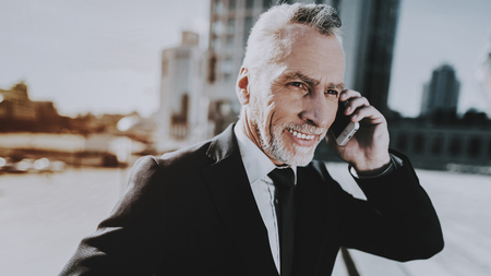 Businessman is Talking on Mobile Phone. Businessman is Old Smiling Man. Man Wearing in Black Suit. Man Looking to Distance. Businessman is Standing on Roof of Skyscraper. Sunny Daytime.
