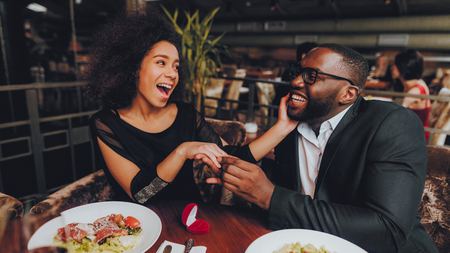 African Handsome Man Proposing to Girlfriend. Romantic Couple in Love Dating. Cutel Man and Girl in a Restaurant. Romantic Concept. Surprised Attractive Woman Getting a Marriage Proposal. Ring.