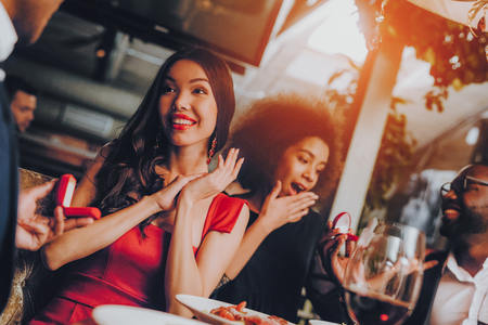 Two Man Friends Proposing Marriage to Girlfriends. Group Happy Friends Enjoying Dating in Restaurant. Double Couple Dating in Restaurant. Romantic Couple in Love Dating. Romantic Concept.