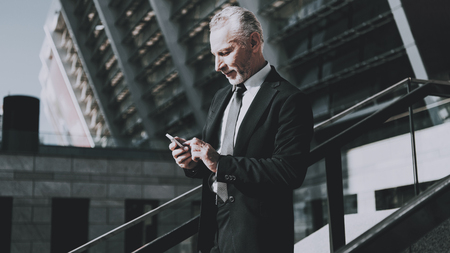 Businessman is Using a Mobile Phone. Man is Watching on Cellphone. Businessman is Old Smiling Man. Man Wearing in Black Suit. Man is Walking on Staircase of Skyscraper. Sunny Daytime. Stock Photo