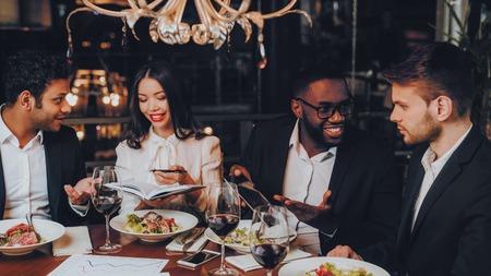 Les gens d'affaires Dîner Réunion Restaurant Concept. Hommes d'affaires ayant une réunion dans un restaurant intérieur. Les gens d'affaires du groupe reçoivent une commande au restaurant. Entreprise, concept de collaboration. Travail en équipe. Banque d'images