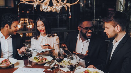 Mensen uit het bedrijfsleven diner vergadering Restaurant Concept. Zakenlieden Die Vergadering In Binnenrestaurant Hebben. Groep zakenmensen die orde krijgen in het restaurant. Zakelijk, samenwerkingsconcept. Teamwerk. Stockfoto