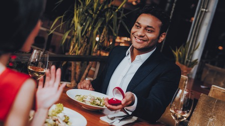 Hispanic Handsome Man Proposing to Girlfriend. Romantic Couple in Love Dating. Cutel Man and Girl in a Restaurant. Romantic Concept. Surprised Attractive Woman Getting a Marriage Proposal.