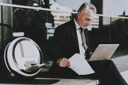 Businessman is Using a Laptop Computer. Businessman is Old Smiling Man. Man Wearing in Black Suit. Man Holding a Papers. Businessman is Sitting on Roof. Monowheel near a Man. Sunny Daytime.