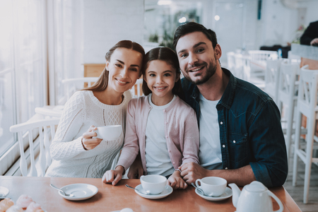 Family Resting in Cafe. Family is a Mother, Father, Daughter and Son. People is Drinking a Tea From Cups. Persons is Sitting at Table. People is Happy and Smiling. Family Portrait. Sunny Daytime. Stock Photo