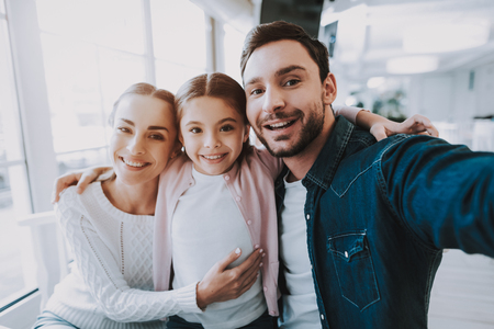 Family Resting in Cafe. Family is a Mother, Father and Daughter. People is Doing Selfie on Mobile Phone. Persons is Sitting at Table. People is Happy and Smiling. Family Portrait. Sunny Daytime.