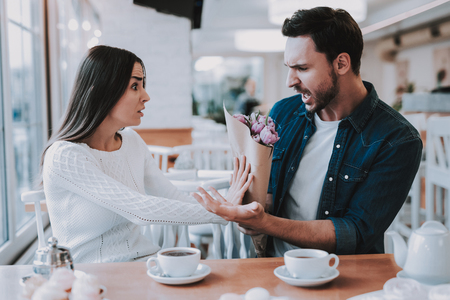 Couple in Cafe. Couple is Beautiful Young Man and Woman. Man is Giving a Bouquet of Flowers to Woman. Woman Dont Want Take a Flowers. Persons is Sitting at Table. Woman is Surprised. Man is Angry.