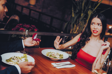 Man Proposing Engagement Ring and Getting Denied. Romantic Hispanic Couple in Love Dating. Cutel Man and Girl in a Restaurant. Romantic Concept. Negative Reaction to Proposing. Disappointment. Фото со стока