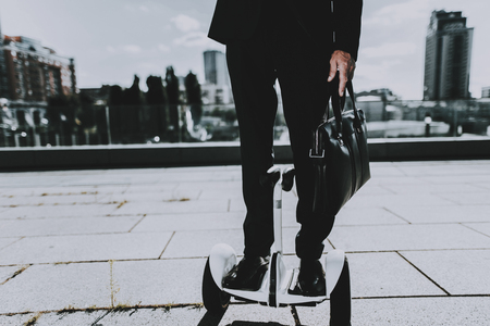 Businessman is Riding on scooter. Businessman is Old Man. Man Wearing in Black Suit. Man is Holding a Briefcase. Businessman on Roof of Skyscraper. Sunny Daytime. City on Background. Down View. Stock Photo