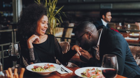 African American Couple Dating in Restaurant. Romantic Couple in Love Dating. Cheerful Man and Woman with Menu in a Restaurant Making Order. Romantic Concept. Man Kissing Girls Hand. Stock Photo - 113609069