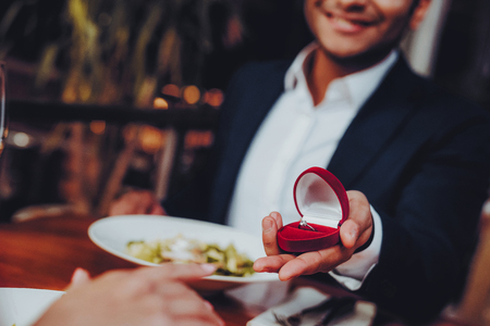 Close Up Handsome Man Proposing to Girlfriend. Romantic Couple in Love Dating. Cutel Man and Girl in a Restaurant. Romantic Concept. Surprised Attractive Woman Getting a Marriage Proposal.