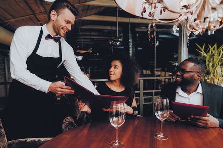 African American Couple Making Order in Restaurant. Romantic Couple in Love Dating. Cheerful Man and Woman with Menu in a Restaurant Making Order. Romantic Concept. Anniversary. Date. Love. Waiter.