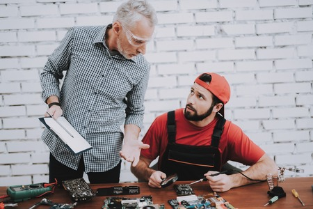 Old Manager Checking Motherboard near Worker. Worker with Tools. Computer Hardware. Young and Old Workers. Modern Devices. Digital Device. Wooden Table. Electronic Devices Concept.