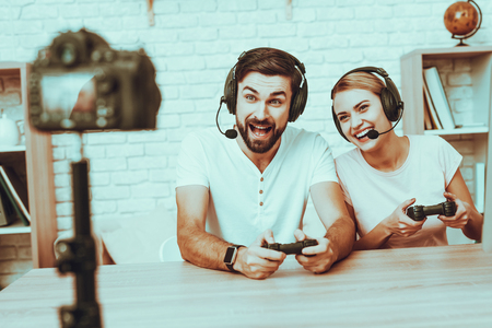 Bloggers Makes a Video. Bloggers is Gamers is Man and Woman. Camera Shoots a Video. People Wearing a Headphones. People Playing a Video Game on Console. People Looking into a Camera. Studio Interior.