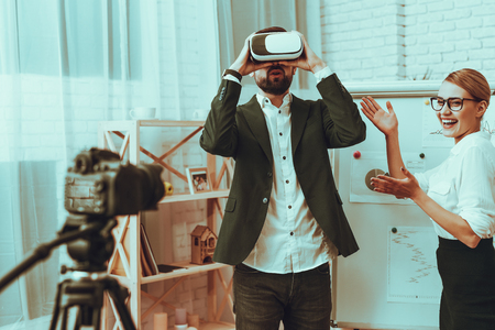 Bloggers Makes a Video. Bloggers is Businessman and Businesswoman. Video About a Innovation. Camera Shoots a Video. Woman Showing a Man. Man Wearing a Virtual Reality Glasses. Studio Interior.
