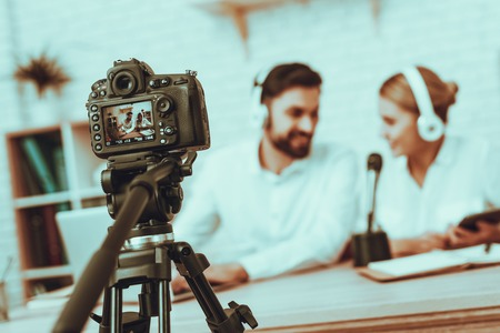 Blur Image of Bloggers Makes a Video. Bloggers is Smiling Man and Woman. Camera Shoots a Video. People Wearing a Headphones. Persons is Talking at Microphone. People in Studio Interior.