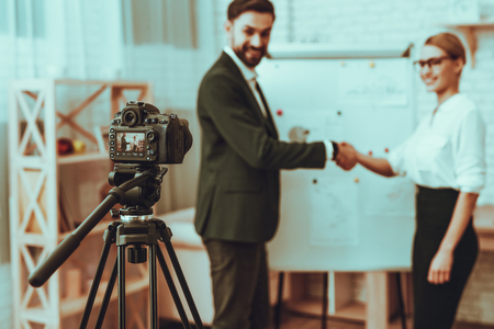 Blur of Bloggers Makes a Video. Bloggers is Businessman and Businesswoman. Video About a Business. Camera Shoots a Video. Businessman and Businesswoman is Handshaking. Business Graph. Studio Interior.