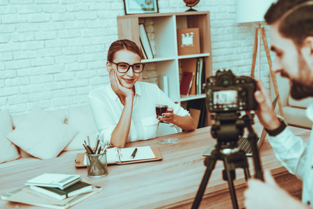 Blogger Makes a Video. Blogger is Smiling Businesswoman. Video About a Business. Man Operator Shoots a Video on Camera. Laptop and Supplies on Table. Woman Drinking a Tea. People in Studio Interior. Banque d'images