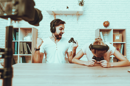 Bloggers Makes a Video. Bloggers is Gamers. Bloggers is Happy Man and Upset Woman. Camera Shoots a Video. People Wearing a Headphones. People Playing a Video Game on Console. Studio Interior. Stock Photo