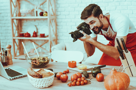 Photographer Makes a Photo. Photographer is Young Beard Man. Man is Taking Picture of Cooking a Food. Guy is Using a Photo Camera. Laptop and Different Food on Table. Man in Studio Interior.