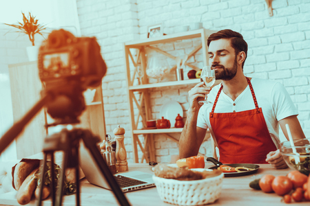 Blogger Makes a Video. Blogger is Young Beard Man. Video About a Cooking. Camera Shoots a Video. Laptop and Different Food on Table. Man Sniffing a White Wine in Wineglass. Man in Studio Interior.