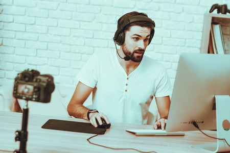 Blogger Makes a Video. Blogger is Gamer. Blogger is Young Beard Man. Camera Shoots a Video. Man in Headphones Playing a Video Game on Computer. Man Looking at a Monitor. Studio Interior. Stock Photo