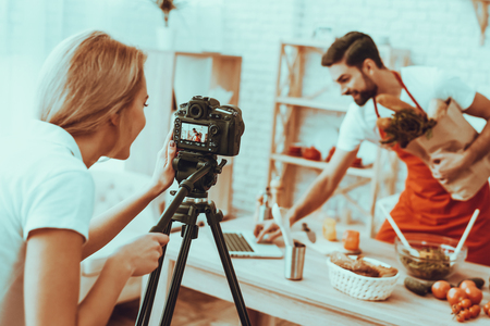 Happy Man Blogger Makes a Video. Video About a Cooking. Woman Operator Shoots a Video on Camera. Different Food on Table. Man Holding a Products and Using a Laptop. People in Studio Interior.