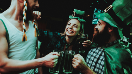 Two Men And Girl In Carnival Hats Drinking Beer. St Patricks Day Celebrating Concept. Bar Counter. Bearded Males. Good Festive Mood. Bright Lights. Club Visitors. Having Fun. Resting Together.