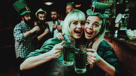 Two Girls In Carnival Clothes. St Patrick's Day Celebrating Concept. Bar Counter. Good Festive Mood. Bright Lights. Club Visitors. Having Fun. Resting Together. Drinking Beer From Glass. Фото со стока