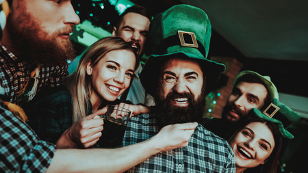Black Bearded Man With Company. St Patricks Day. Bar Counter. Alcohol Handling. Smiling Teenagers. Good Festive Mood. Bright Lights. Funny Club Visitors. Celebrating Together. Night Party. 写真素材