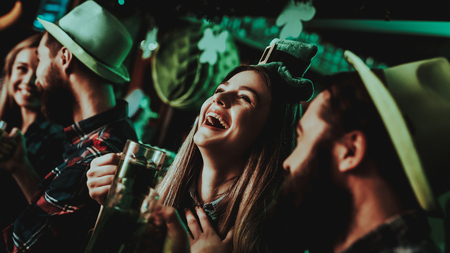 Young Company Are Celebrating St Patricks Day. Bar Counter. Alcohol Handling. Black Beard. Smiling Teenagers. Carnival Clothes. Bright Lights. Club Visitors. Funny Hats. Beer Drinking.