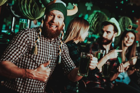Man In Funny Hat Celebrates St Patricks Day. Bar Counter. Alcohol Handling. Ginger Beard. Smiling Male. Good Festive Mood. Bright Lights. Funny Club Visitor. Thumbs Up. Glass Of Beer. Stock Photo