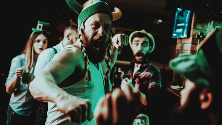 Two Men Fight In Pub. Saint Patricks Day Concept. Punch In The Face. Quarrel In The Bar. White Singlet. Agressive Males. Angry Guys. Violence In The Club. Funny Hats. Bright Lights. Reklamní fotografie