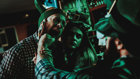 Two Men Fight In Pub. Saint Patricks Day Concept. Punch In The Face. Quarrel In The Bar. Plaid Flannel. Agressive Males. Angry Guys. Violence In The Club. Knock Out. Bright Lights.