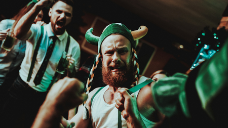 Two Men Fight In Pub. Saint Patricks Day Concept. Punch In The Face. Quarrel In The Bar. White Singlet. Agressive Males. Angry Guys. Violence In The Club. Funny Hats. Bright Lights. Stock Photo