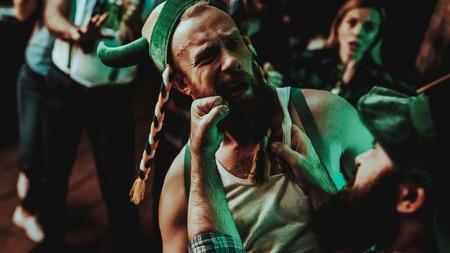 Zwei Männer kämpfen in der Kneipe. St. Patrick's Day-Konzept. Schlag ins Gesicht. Streit in der Bar. Weißes Unterhemd. Aggressive Männer. Wütende Jungs. Gewalt im Club. Witzige Hüte. Helle Lichter.