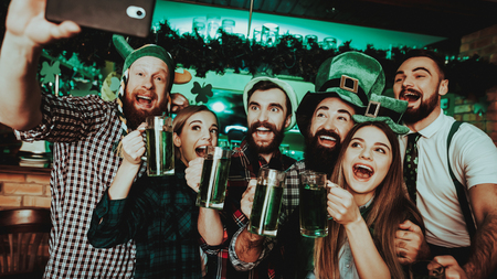 Young Company Do Selfie In Pub. St Patricks Day. Bar Counter. Alcohol Handling. Black Beard. Smiling Teenagers. Good Festive Mood. Bright Lights. Club Visitors. Funny Hats. Glasses With Beer.