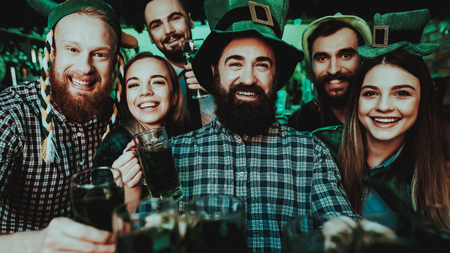 A company of young people posing on the camera with glasses of beer in their hands. They celebrate St. Patricks Day at the pub. They are very fun. Imagens